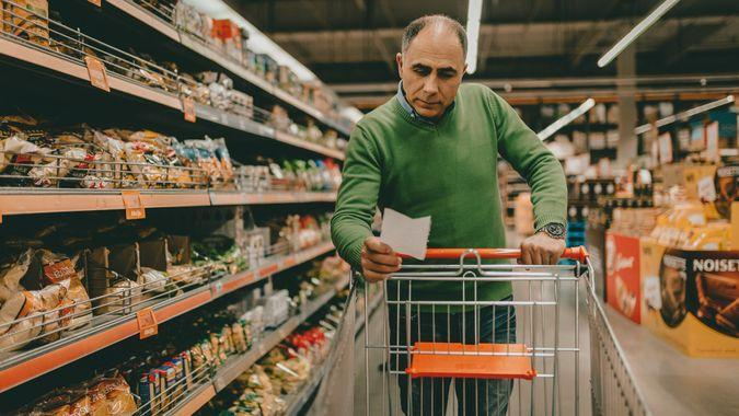 Mature man with a shopping list buying groceries in the supermarket.