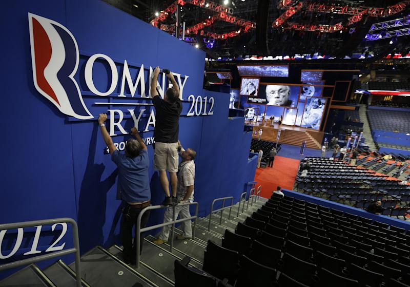 Workers place Romney-Ryan campaign sign inside of the Tampa Bay Times Forum at the Republican National Convention in Tampa, Fla., on Sunday, Aug. 26, 2012, as pictures of Neil Armstrong, the first man to walk on the moon, are displayed on the main stage. (AP Photo/David Goldman)