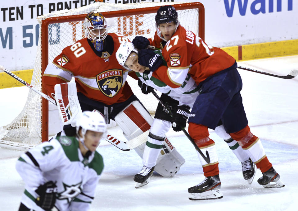 Dallas Stars left wing Joel Kiviranta (25) gets pushed by Florida Panthers center Eetu Luostarinen (27) as goaltender Chris Driedger (60) looks on during the first period of an NHL hockey game Wednesday, Feb. 24, 2021, in Sunrise, Fla. (AP Photo/Jim Rassol)
