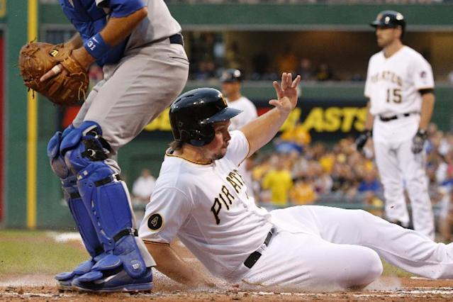 Pittsburgh Pirates' Travis Snider, front right, scores on a sacrifice fly by teammate Ike Davis (15) off Los Angeles Dodgers starting pitcher Dan Haren during the first inning of a baseball game in Pittsburgh, Wednesday, July 23, 2014. (AP Photo)