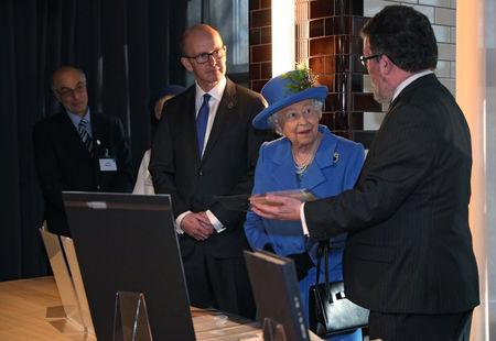 Britain's Queen Elizabeth looks at artefacts as she meets with GCHQ Director Jeremy Fleming and historian Tony Comer during her visit at the Watergate House to mark the centenary of the GCHQ (Government Communications Head Quarters) in London, Britain, February 14, 2019. REUTERS/Hannah McKay/Pool