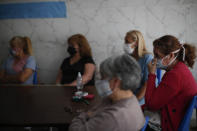 Former workers sit inside San Andres Clinic which they have been occupying since it closed at the start of the year following the death of the hospital's director and owner in Caseros, Argentina, Friday, April 30, 2021. While the pandemic has swelled the need for hospital beds, many private clinics say they're struggling to survive, citing the pandemic having pushed away many non-COVID patients and losing money on coronavirus sufferers because the government insurance program doesn't pay enough to meet costs. (AP Photo/Natacha Pisarenko)