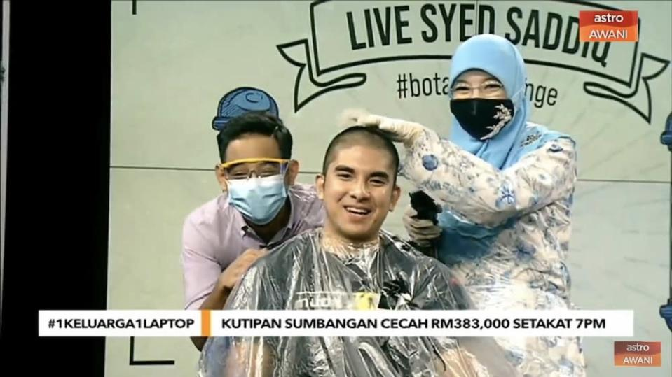 Syed Saddiq puts on a game face as his head is shaved. — Screencap via AstroAwani/Twitter