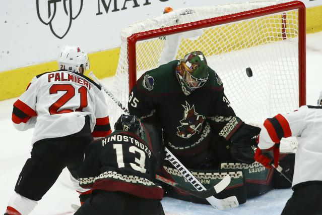 New Jersey Devils right wing Kyle Palmieri (21) scores a goal against Arizona Coyotes goaltender Darcy Kuemper (35) as Coyotes right wing Vinnie Hinostroza (13) defends late during the third period of an NHL hockey game, Saturday, Dec. 14, 2019, in Glendale, Ariz. The Devils defeated the Coyotes 2-1. (AP Photo/Ross D. Franklin)