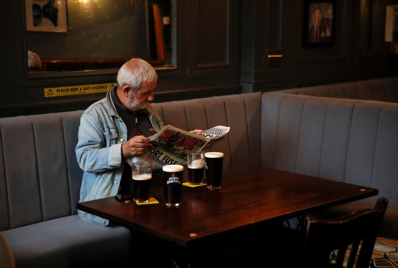 A man reads a newspaper as he sits inside the Grapes pub in Liverpool