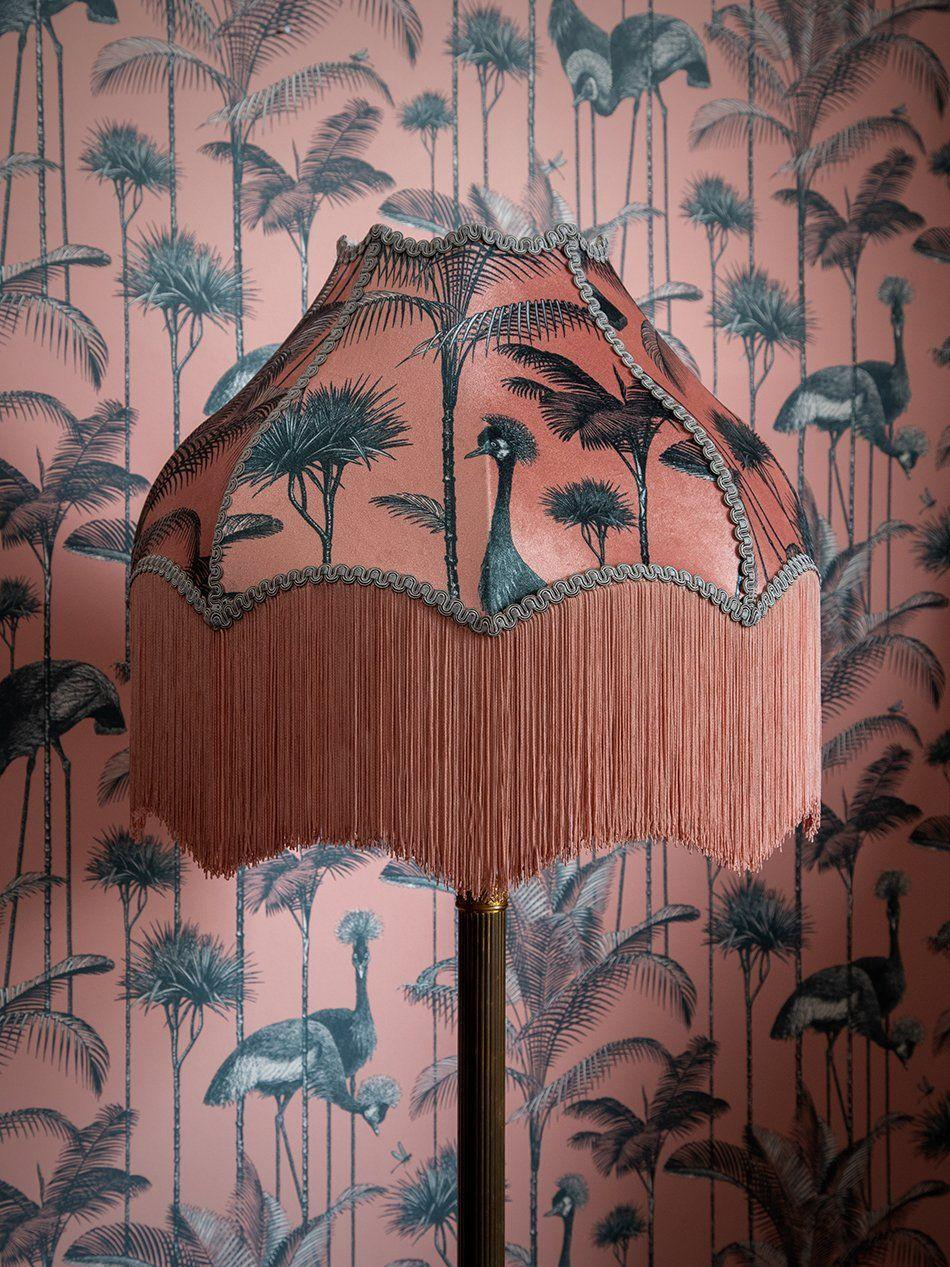 """<p>For the fearless decorator. This classic curved lampshade with decorative fringing has been updated in a coral velvet with a fabulous crane and palm tree print. A romantic and dramatic addition to a seriously stylish home. </p><p><strong>Shop now: <a href=""""https://divinesavages.com/products/crane-fonda-coral-lampshade?_pos=3&_sid=f130c006d&_ss=r"""" rel=""""nofollow noopener"""" target=""""_blank"""" data-ylk=""""slk:Crane Fonda Coral Lampshade at Divine Savages"""" class=""""link rapid-noclick-resp"""">Crane Fonda Coral Lampshade at Divine Savages</a></strong></p>"""