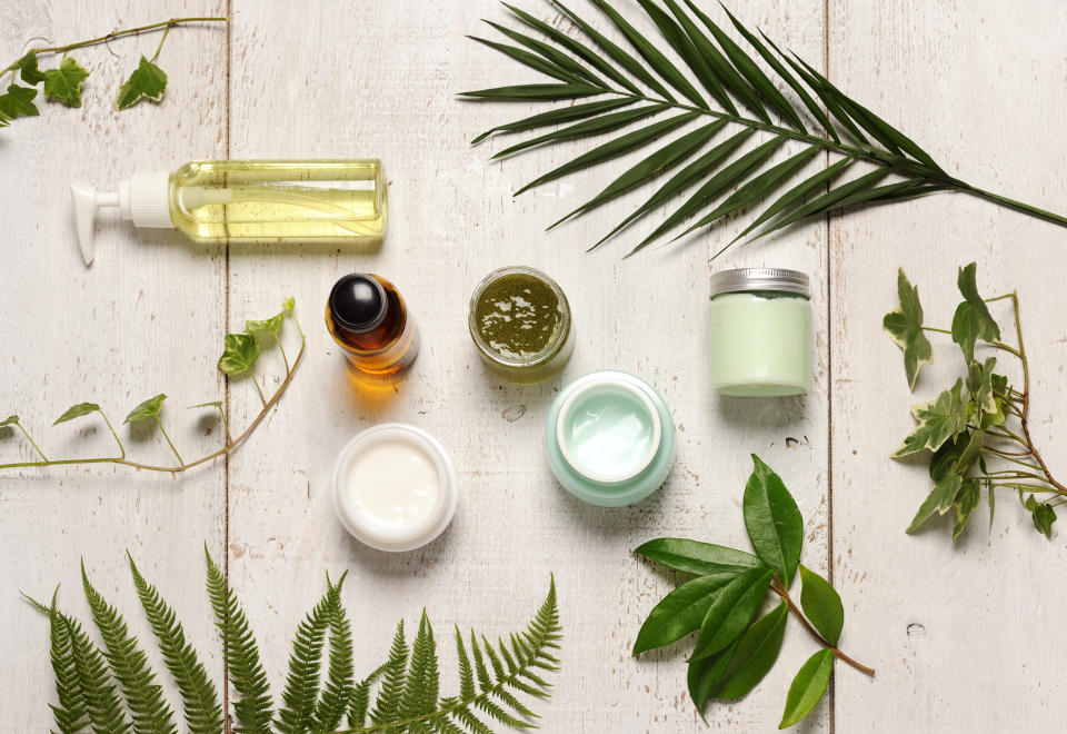 composition of containers with cosmetics and green leaves