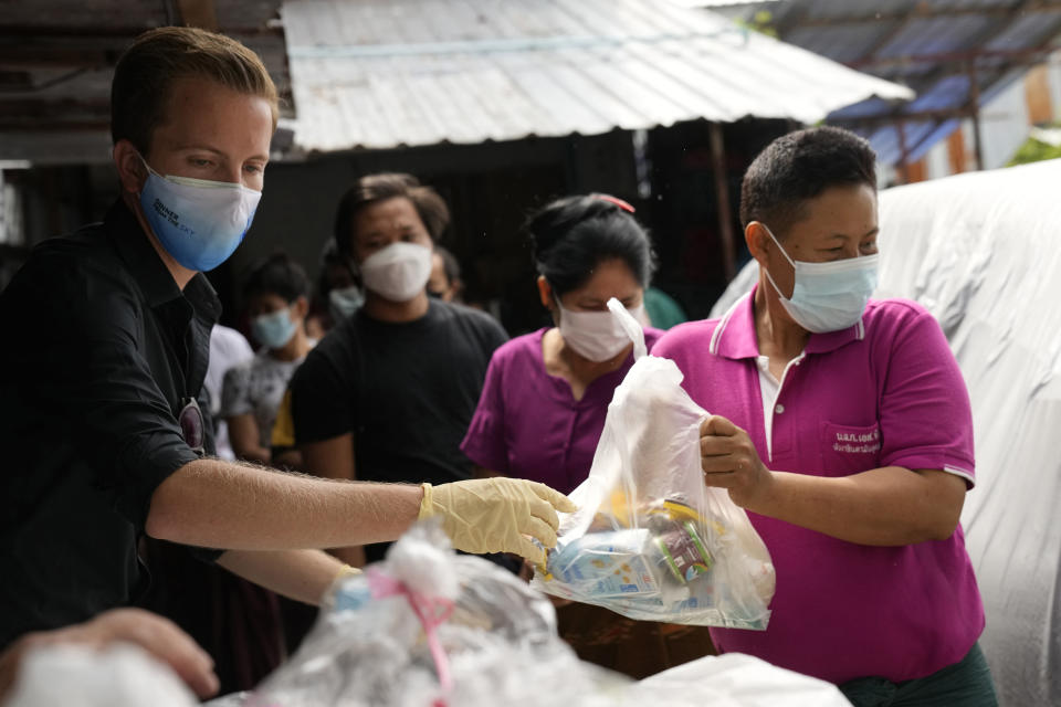 Bangkok Community Help Foundation co-founder Friso Poldervaart, left, from the Netherlands distributes food supplies at a construction camp in Bangkok, Thailand, on Aug. 31, 2021. In Thailand's worst coronavirus surge yet, lockdown measures have reduced what little Bangkok's have-nots had to zero. Their plight has given rise to volunteer groups working to ensure the poorest survive. (AP Photo/Sakchai Lalit)