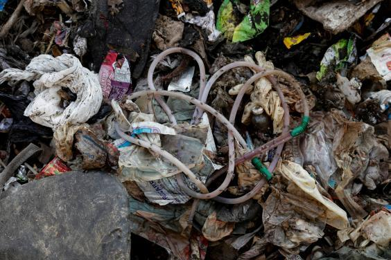 Disposed medical waste lies on the floor of a landfill site (Reuters)