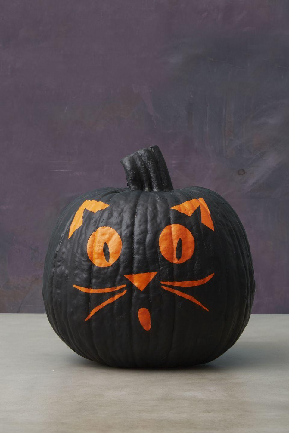 <p>Fashion feline features from blue painter's tape and adhere to an orange pumpkin before giving it a once-over with black acrylic paint. Once it's dry, remove the stencils for one cute cat. See? It doesn't matter if you paint outside the lines. </p>