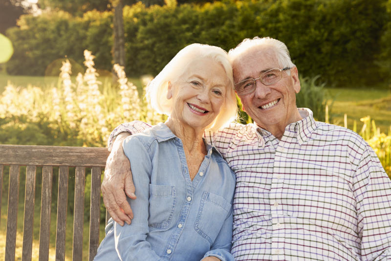Senior couple sitting on wooden bench outdoors, smiling