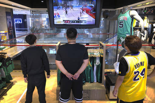Employees watch a live broadcast of Game 5 of the NBA Finals at an NBA store in Beijing, Saturday, Oct. 10, 2020. The NBA is returning to Chinese state television after a one-year absence. CCTV announced Friday that it would air Game 5 of the NBA Finals between the Los Angeles Lakers and Miami Heat the first time that the league would appear on the network since the rift that started when Houston Rockets general manager Daryl Morey tweeted support for anti-government protesters in Hong Kong. (AP Photo/Mark Schiefelbein)