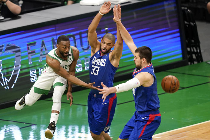 Boston Celtics guard Kemba Walker, left, passes the ball in between LA Clippers forward Nicolas Batum (33) and center Ivica Zubac, right, in the first quarter of an NBA basketball game, Tuesday, March 2, 2021, in Boston. (AP Photo/Elise Amendola)