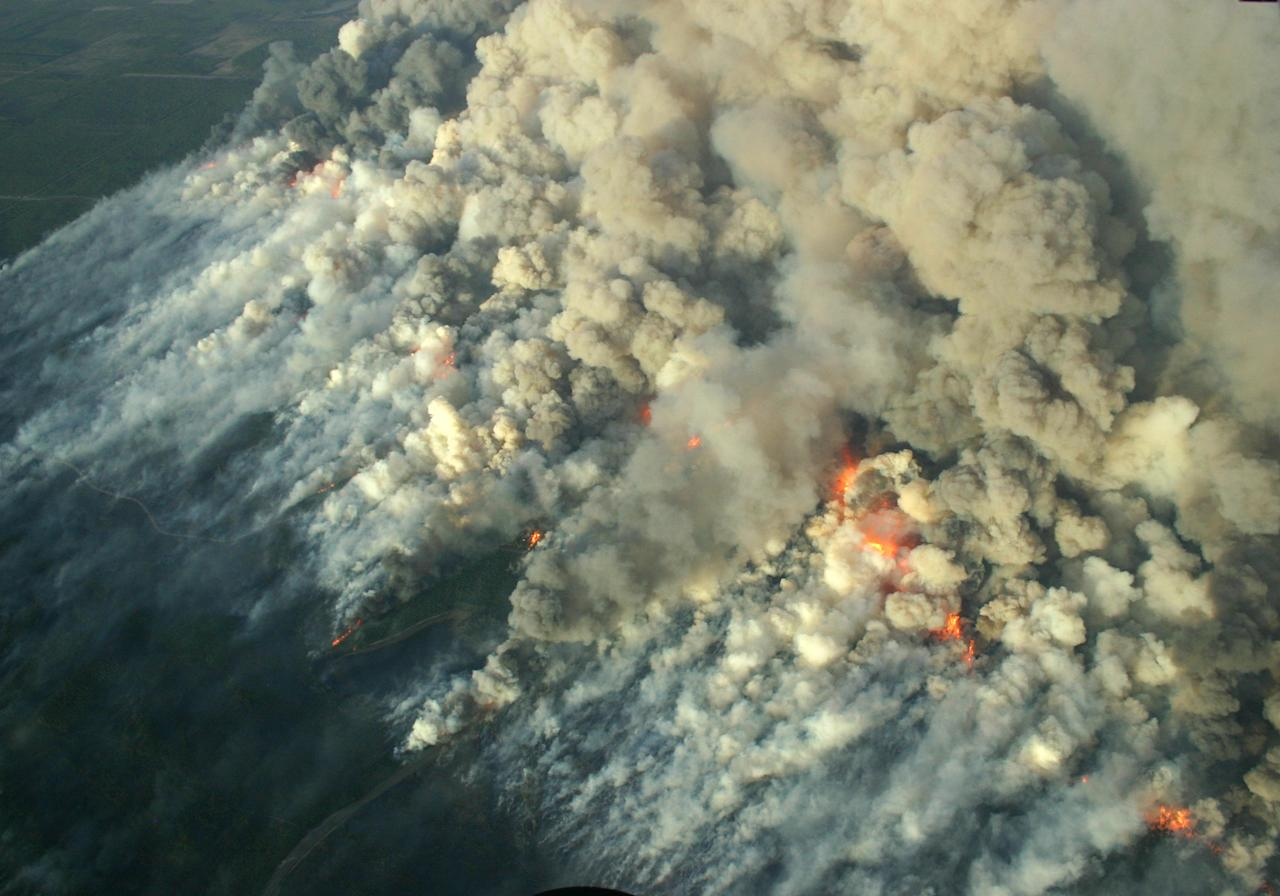 This May 14, 2013, photo provided by the Wisconsoin Department of Natural Resources shows a smoky wildfire in northwestern Wisconsin that has consumed 8,700 acres, destroyed nearly 50 structures and forced dozens from their homes. The DNR says the wildfire in Douglas County is about 90 percent contained Wednesday morning, meaning firefighters have stopped most of the fire from spreading. (AP Photo/Wisconsoin Department of Natural Resources)