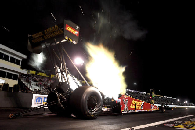 In this photo provided by the NHRA, Top Fuel driver Brittany Force takes part in the first day of qualifying for the Mopar Express Lane NHRA Nationals drag races in Mohnton, Pa. Force had a run of 3.651 seconds at 332.92 mph to break the track time record. (Marc Gewertz/NHRA via AP)