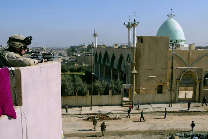 A US soldier scans the area in front of a mosque suspected to support insurgents in the city of Mosul on February 25, 2005 (AFP Photo/Mauricio Lima)