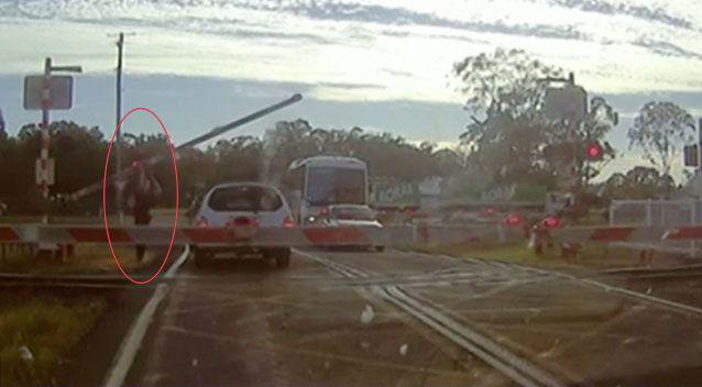 The quick-thinking officer ducked under the first boom gate and forced the second up, allowing the woman to drive off before the train approached. Picture: Queensland Police