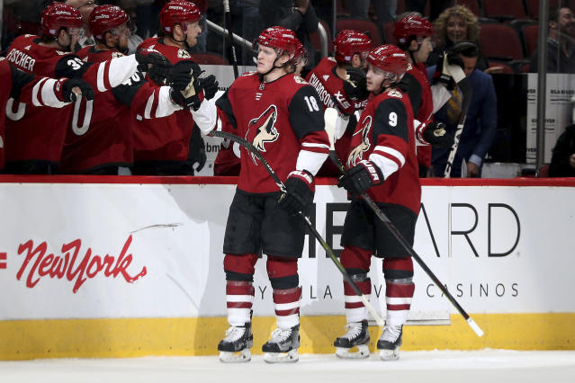 Arizona Coyotes' Christian Dvorak (18) and Clayton Keller (9) are greeted by teammates after Dvorak's first goal against the Anaheim Ducks during the first period of an NHL hockey game Wednesday, Nov. 27, 2019, in Glendale, Ariz. (AP Photo/Darryl Webb)
