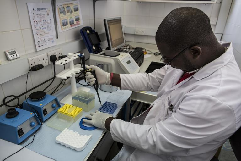 A lab technician works in the viral load room at the Thyolo District hospital in Malawi in November, 2014