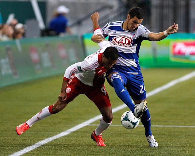 Timbers forward Ryan Johnson (9( and FC Dallas defender (24) Matt Hedges run with locked arms as they fight for the ball in the first half. The Portland Timbers led FC Dallas 2-1 at half in Portland Saturday Aug. 17, 2013. (AP Photo/The Oregonian, Doug Beghtel)