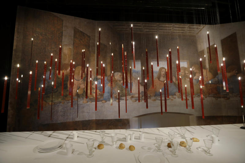 Suspension lamp called 'Flying Flames' designed by german designer Ingo Mauer is displayed at Milan's Design Fair, in Milan, Italy, Friday, April 12, 2013. The Milan furniture and design week fair is a six-day event which ends next Sunday. (AP Photo/Luca Bruno)