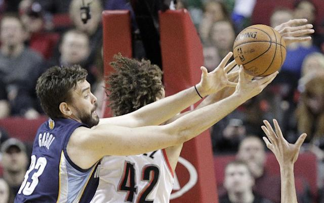 Memphis Grizzlies center Marc Gasol, left, of Spain, pulls in a rebound against Portland Trail Blazers center Robin Lopez during the first half of an NBA basketball game in Portland, Ore., Tuesday, Jan. 28, 2014. (AP Photo/Don Ryan)