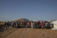 Tigray refugees who fled the conflict in Ethiopia's Tigray region, are ordered to organize themselves in line to receive aid at Umm Rakouba refugee camp in Qadarif, eastern Sudan, Tuesday, Nov. 24, 2020. (AP Photo/Nariman El-Mofty)