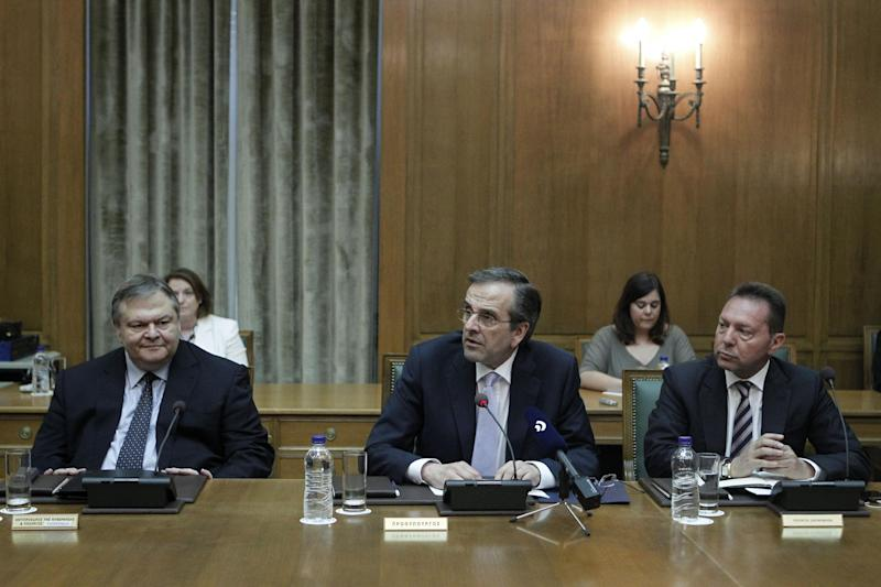Greece's Prime Minister Antonis Samaras, center, Socialist party head Evangelos Venizelos, who was named Deputy Prime Minister and Foreign Minister, and Finance Minister Yannis Stournaras, right, attend a new cabinet meeting, in which the prime minister handed key posts to the coalition government's minority Socialist party in Athens, on Tuesday , June 25, 2013. Samaras stressed the need for stability and unity Tuesday, outlining his new cabinet's priorities following a broad reshuffle triggered by Greece's latest political crisis. (AP Photo/Petros Giannakouris)