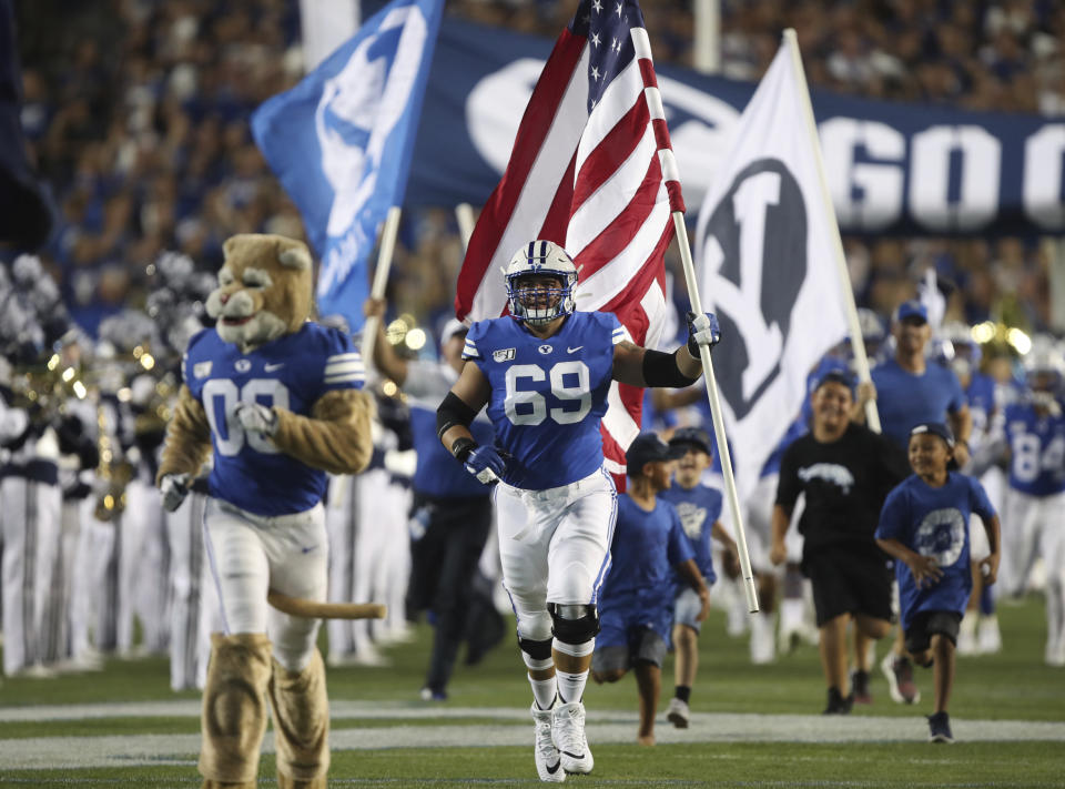 BYU offensive lineman Tristen Hoge (69) brings the American flag onto the field before an NCAA college football game against Utah, Thursday, Aug. 29, 2019, in Provo, Utah. (AP Photo/George Frey)
