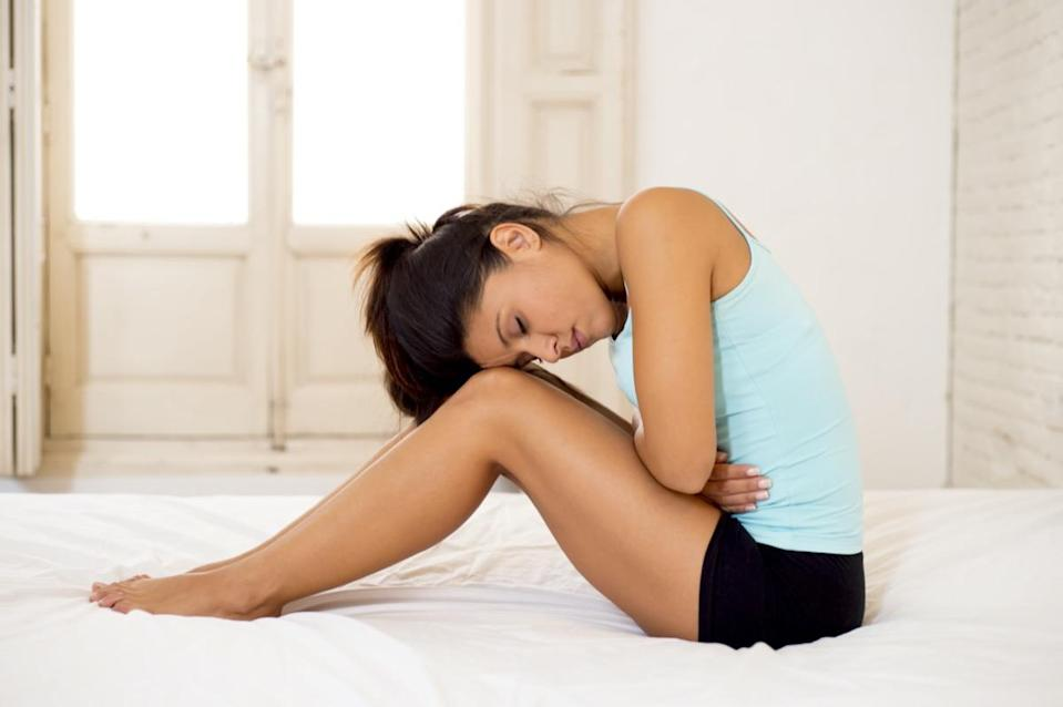 woman in painful expression holding her belly suffering menstrual period pain lying sad on home bed having tummy cramp