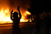 FILE - In this Aug. 24, 2020, file photo, protesters walk past police with their arms up, in Kenosha, Wis., as a building burns in the background. The federal government deliberately targeted Black Lives Matter protesters via heavy-handed criminal prosecutions in an attempt to disrupt and discourage the global movement that swept the nation last summer in the wake of the police killing of George Floyd, according to a new report released Wednesday, Aug. 18, 2021, by The Movement for Black Lives. (AP Photo/David Goldman, File)