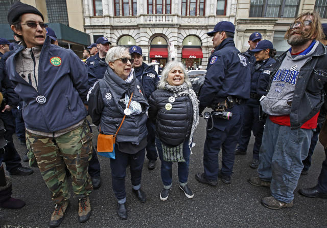 <p>Deportation protesters arrested as they supported the director of Judson Church's New Sanctuary Coalition shout slogans as they wait for police to load them into squad cars and other police vehicles for transfer to booking, Jan. 11, 2018, in New York. (Photo: Kathy Willens/AP) </p>