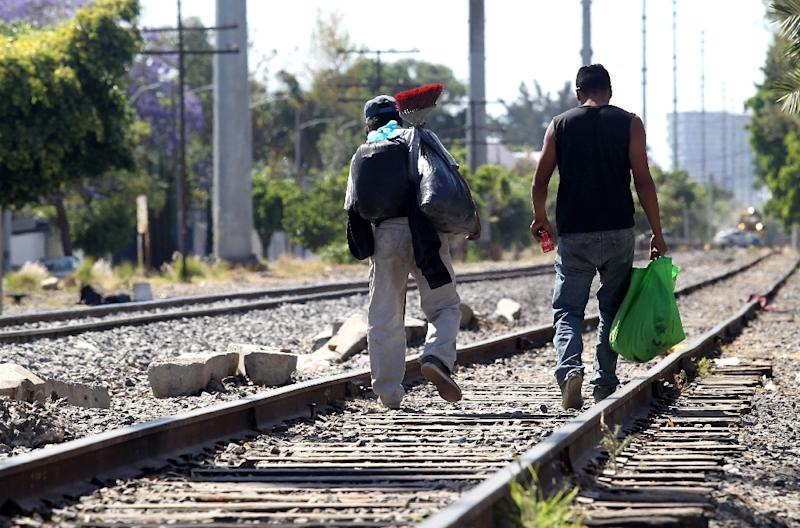 "Central American migrants walk along the train lines in Mexico preparing to jump on ""The Beast,"" a train that will take them to the border with the United States (AFP Photo/ULISES RUIZ)"