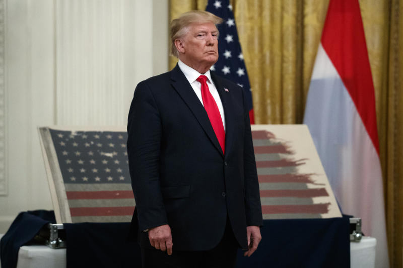President Donald Trump stands in front of a 48-star flag flown on a U.S. Naval vessel during the D-Day invasion during a ceremony in the East Room of the White House, Thursday, July 18, 2019, in Washington. The flag, presented by its Dutch owners to Trump, will be given to the Smithsonian's National Museum of American History. The vessel was control vessel Landing Craft, Control 60 (LCC 60). (AP Photo/Carolyn Kaster)