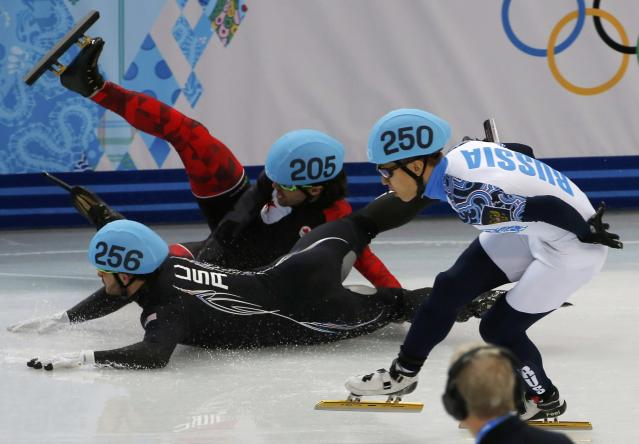 Canada's Charles Hamelin (back) and Eduardo Alvarez of the U.S. (front) fall as Russia's Victor An (R) skates past during the men's 1,000 metres short track speed skating quarter-finals race at the Iceberg Skating Palace at the Sochi 2014 Winter Olympic Games February 15, 2014. REUTERS/Eric Gaillard (RUSSIA - Tags: OLYMPICS SPORT SPEED SKATING)