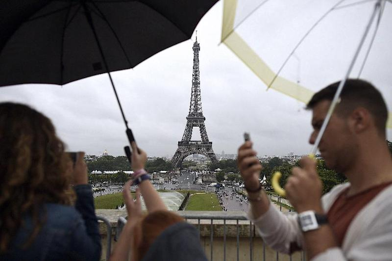 Tourists take pictures in the rain in front of the Eiffel Tower on August 8, 2014, in Paris