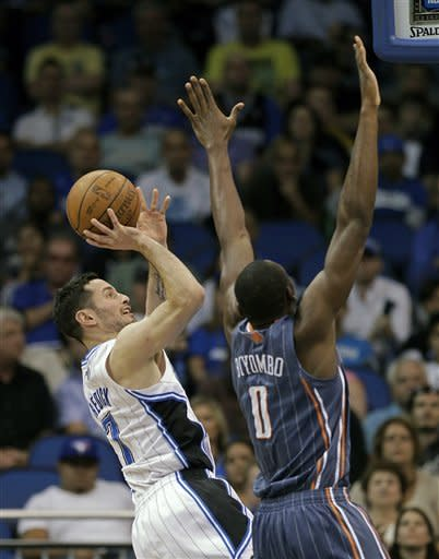 Orlando Magic's J.J. Redick, left, takes a shot over Charlotte Bobcats' Bismack Biyombo (0) during the first half of an NBA basketball game, Wednesday, April 25, 2012, in Orlando, Fla. (AP Photo/John Raoux)