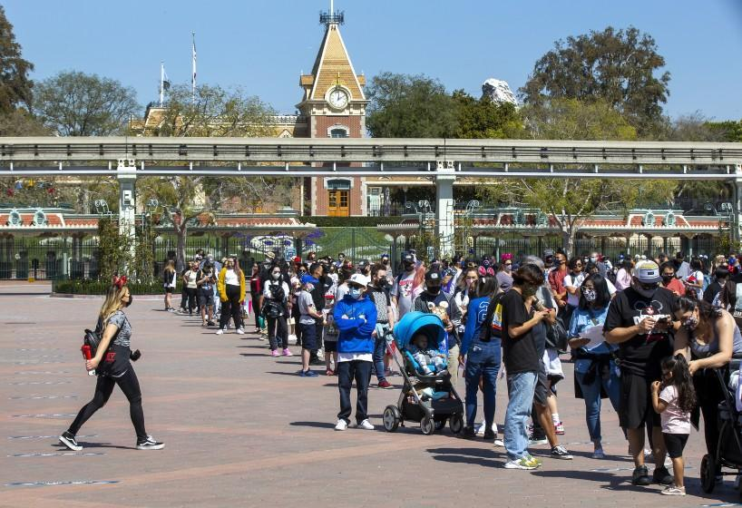 """ANAHEIM, CA - March 18: With a view of Disneyland behind them, Disney fans wait in line to attend the debut of Disney California Adventure's """"A Touch of Disney."""""""