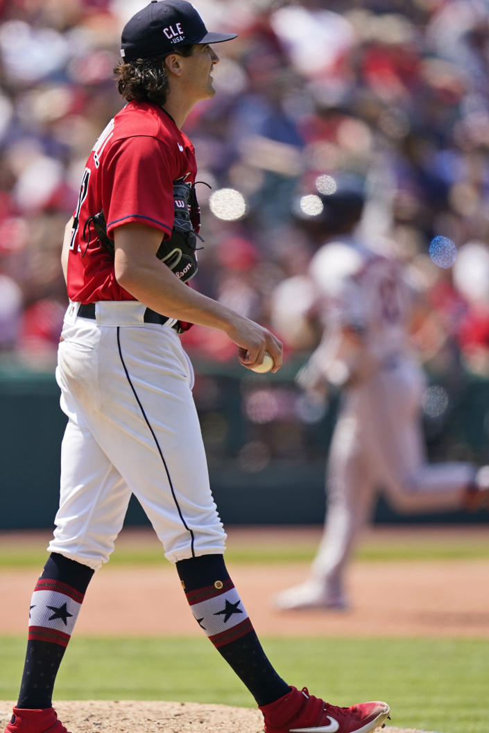 Cleveland Indians starting pitcher Cal Quantrill, left, waits for Houston Astros' Chas McCormick to run the bases after McCormick hit a two run home run in the sixth inning of a baseball game, Sunday, July 4, 2021, in Cleveland. (AP Photo/Tony Dejak)