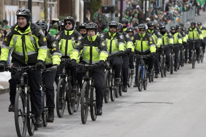 FILE - In this March 19, 2017, file photo, Boston Police patrol on bicycles during the annual St. Patrick's Day Parade in Boston. The city's police department remains largely white, despite vows for years by city leaders to work toward making the police force look more like the community it serves. (AP Photo/Michael Dwyer, File)