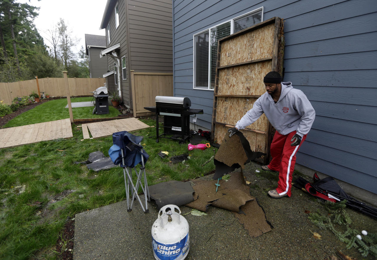 Ralph Jenkins clears debris from his backyard, including roofing materials and a large wooden panel from his neighbor's carport, in the Frederickson neighborhood near Puyallup, Wash., Monday, Sept. 30, 2013. A tornado swept through the area earlier in the day, causing damage to several dozen homes. (AP Photo/Ted S. Warren)