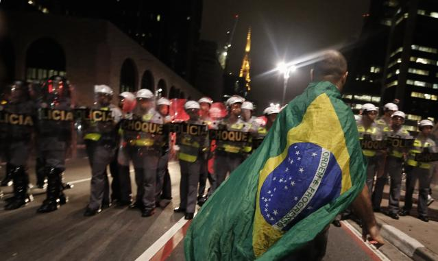 A demonstrator wearing a Brazilian flag walks in front of military policemen during a protest against the 2014 World Cup, in Sao Paulo March 13, 2014. An estimated 1,500 protesters gathered to march the streets of downtown Sao Paulo to show they are against the World Cup and against the costs associated with Brazil's hosting the sporting event. Activists are demanding more money be spent on education, health care, public transportation and to fight crime. REUTERS/Nacho Doce (BRAZIL - Tags: SPORT SOCCER WORLD CUP POLITICS CIVIL UNREST CRIME LAW)