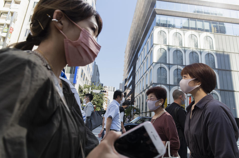 People wearing face masks walk across an intersection in the Ginza shopping district in Tokyo on Thursday, June 10, 2021. (AP Photo/Hiro Komae)