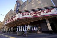 """Employee Grayson Allred walks away with a ladder after working on the front marquee at the Paramount Theatre on Wednesday, Dec. 16, 2020, in Abilene, Texas. The marquee which in part reads, """"It's A Wonderful Life, Cancelled"""", notifies all would-be patrons that the theatre has closed down indefinitely due to rising cases of COVID-19 in the city. (AP Photo/Tony Gutierrez)"""