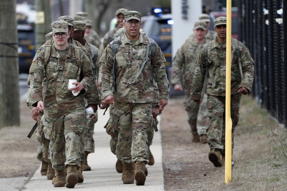 National Guard personnel march in formation as they leave duty after working Thursday, March 19, 2020, at a state-managed coronavirus drive-thru testing site that just opened on Staten Island in New York. (AP Photo/Kathy Willens)