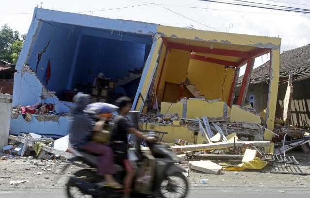 <p>A motorcycle passes buildings destroyed by Sunday's earthquake in North Lombok, Indonesia, Friday, Aug. 10, 2018. (Photo: Firdia Lisnawati/AP) </p>