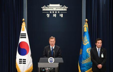 South Korea's new President Moon Jae-In speaks as Prime Minister nominee Lee Nak-Yon listens to during a press conference at the presidential Blue House in Seoul