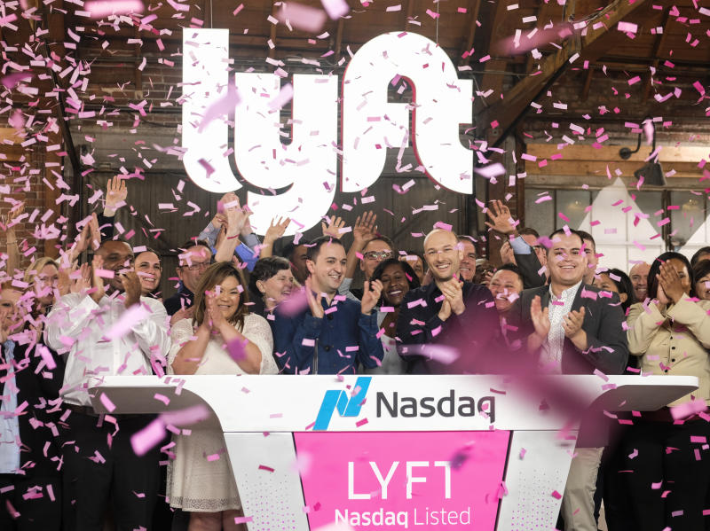 FILE- In this March 29, 2019, file photo Lyft co-founders John Zimmer, front third from left, and Logan Green, front third from right, cheer as they as they ring a ceremonial opening bell in Los Angeles. Lyft gave investors a lesson in how quickly a company's market value can change. The ride-hailing company's stock surged more than 20% from its IPO price on Friday. But by the first hour of Lyft's second day of trading, the stock had fallen below the IPO price of $72. (AP Photo/Ringo H.W. Chiu, File)