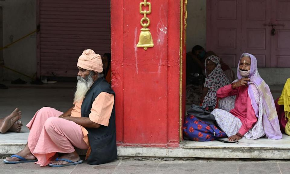 People wait for free food outside a temple in New Delhi