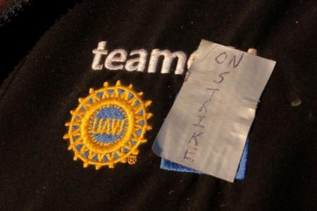 """A striking union worker has taped """"On Strike"""" onto his jacket on the picket line outside the GM Flint Truck Assembly in Flint"""